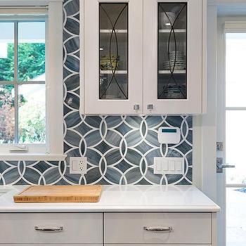 white kitchen cabinets with blue geometric tile backsplash