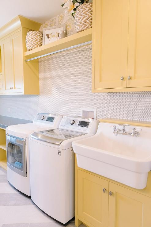 yellow shaker laundry room cabinets with white hex tile