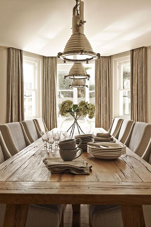 Reclaimed Wood Dining Table Lined With Taupe Curved Arm Chairs Illuminated By Ralph Lauren Home Montauk Pendants Placed In Front Of Bay Windows