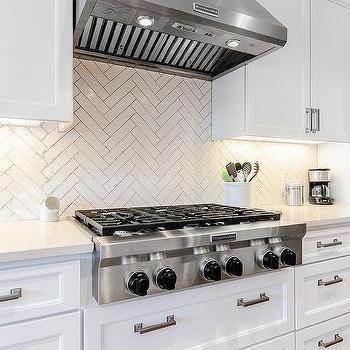 with white quartz countertops and a white herringbone tile backsplash