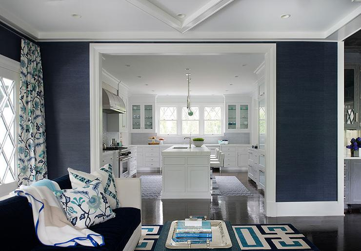 Blue living room features walls clad in navy grasscloth surrounding a white  sofa with velvet cushions facing turquoise ottoman coffee table Navy Sofa Design Ideas