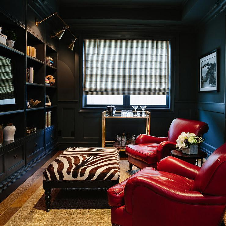Black Paneled Den With Built In Shelves And Brass Picture