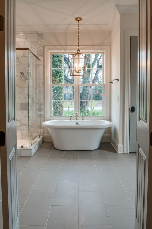 Brass lantern over tub and gray porcelain floor tiles transitional bathroom Tile in master bedroom closet