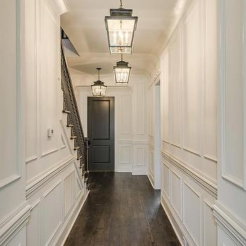 foyer with white full wall wainscoting and black front door - Wainscoting Design Ideas