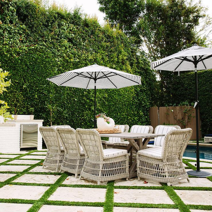 Good Chic Patio Features A Trestle Outdoor Dining Table Lined With Wicker Dining  Chairs Accented With Black And White Striped Umbrellas Atop Grass Pavers.