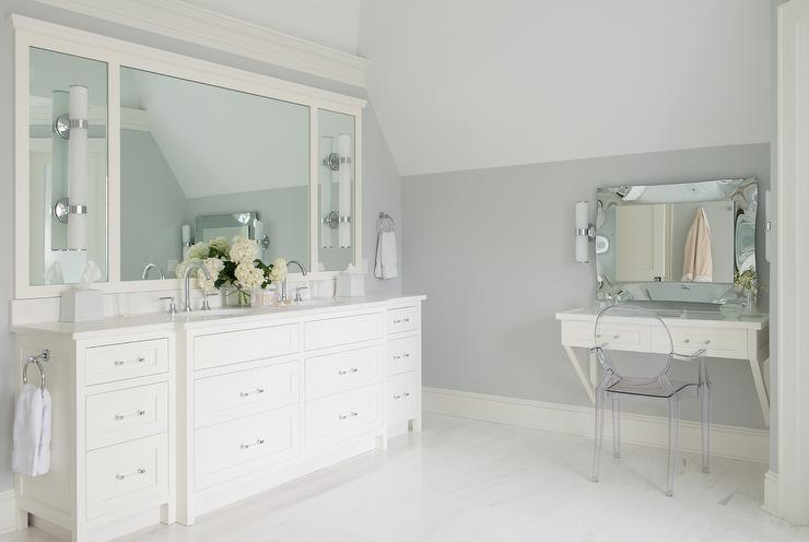 white and gray bathroom features a gray wall lined with an ivory dual washstand fitted with nickel and glass pulls topped with white quartz fitted with his