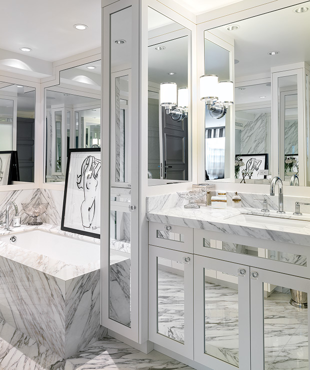 gray bathroom features a gray mirrored washstand topped with gray and white marble under three mirrors next to a tall mirrored linen cabinet