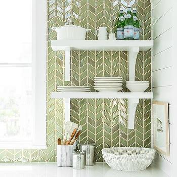 green herringbone tiled backsplash lined with stacked white shelves