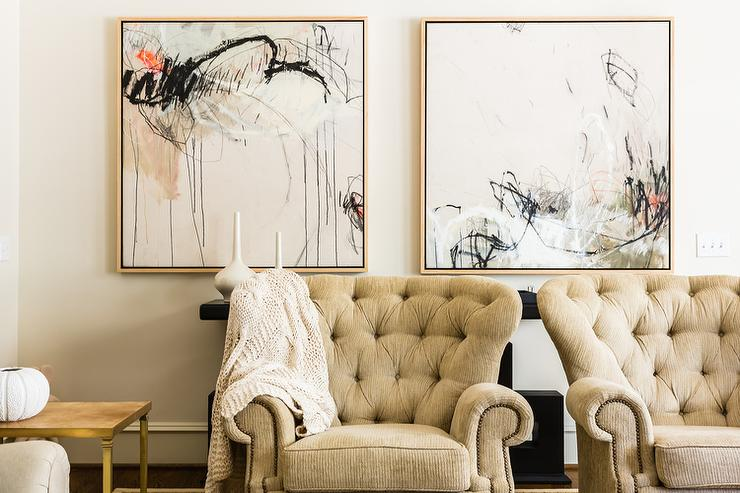Beautiful Living Room Features A Pair Of Cream Tufted Accent Chairs Placed In Front Glossy Black Console Table Under Red And Abstract Art
