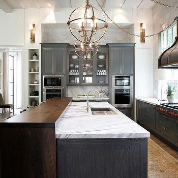 charcoal gray kitchen cabinets with brass sphere pendants glass and carrara marble backsplash glass marble kitchen backsplash