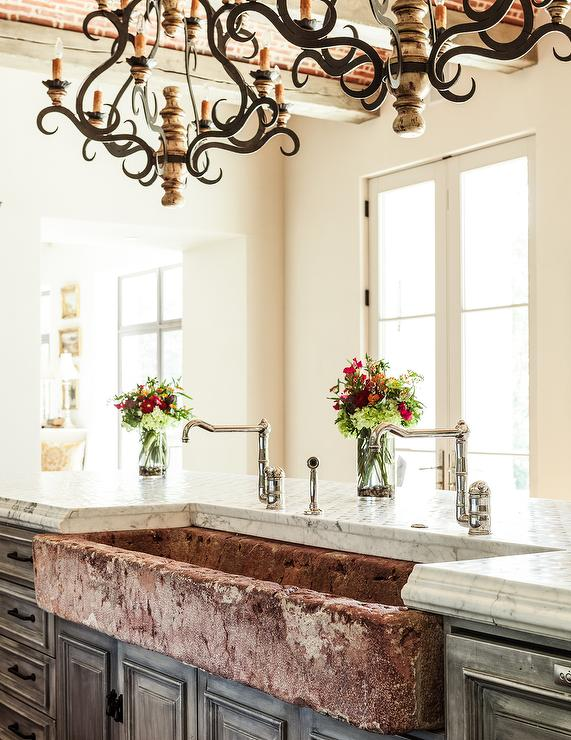 iron and wood chandeliers hang over a gray distressed kitchen island