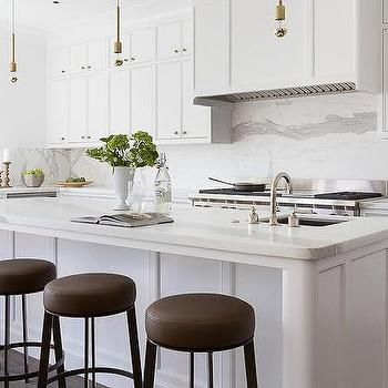 Delicieux White Kitchen Island With Round Brown Leather Barstools And Half Gold Light  Bulb Pendants