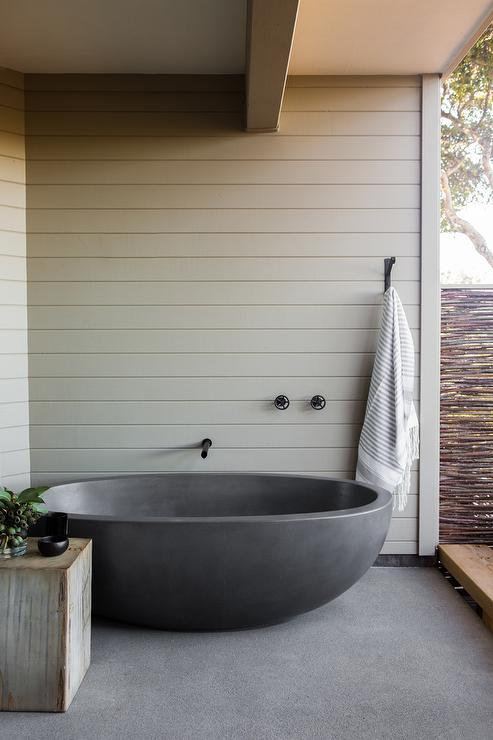 zen outdoor bathroom features a black tub under a wall mount tub filler alongside an iron towel hook