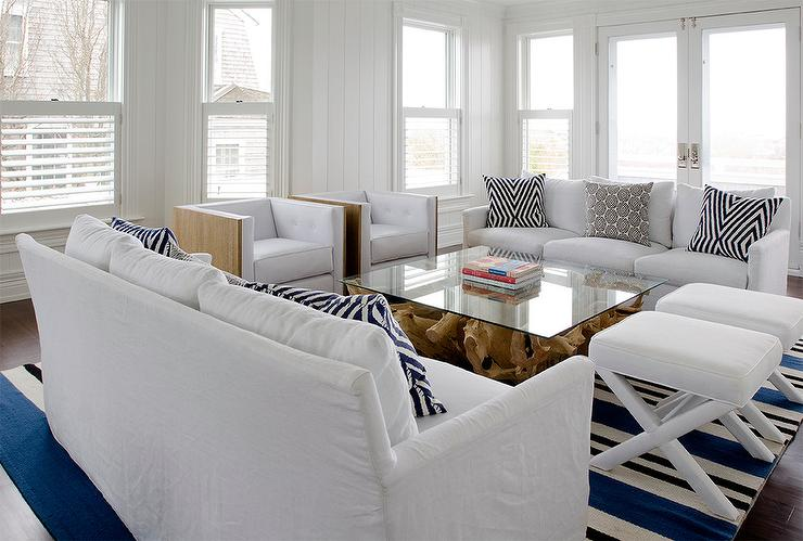 White Living Room Features Sofas Lined With Black And Pillows Facing Each Other Across From A Driftwood Coffee Table Accented Glass Top