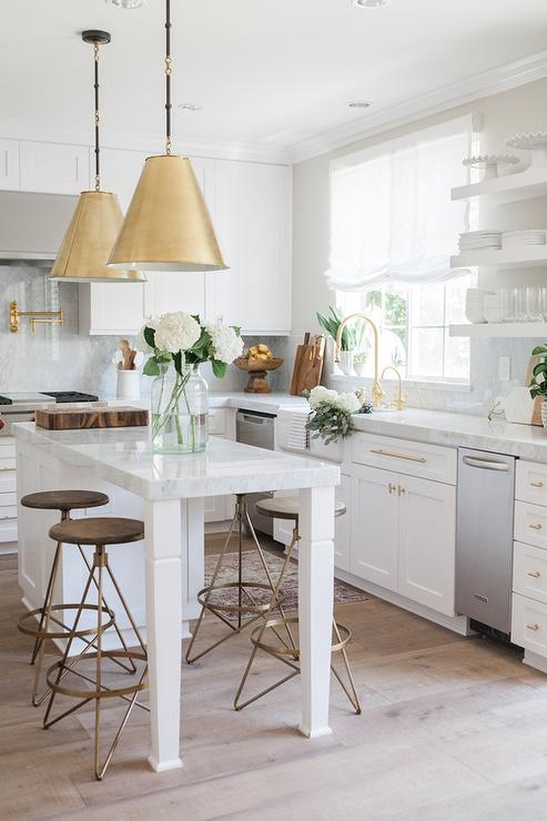 hanging lamps in antique brass stands over a white kitchen island