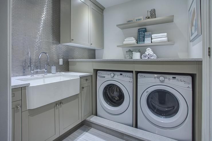 Contemporary Gray Laundry Room Features Gray Shaker Cabinets Paired With  Corian Countertops And A Stainless Steel Mini Brick Tile Backsplash.
