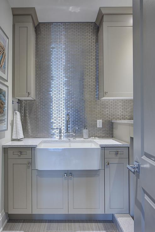 gray laundry cabinets with stainless steel mini brick tile