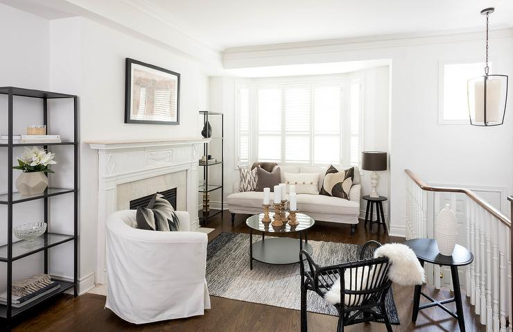 Chic Second Floor Living Room Boasts A Bay Window Dressed In Plantation Shutters Filled With Slipcovered Settee Lined White And Gray Pillows Facing
