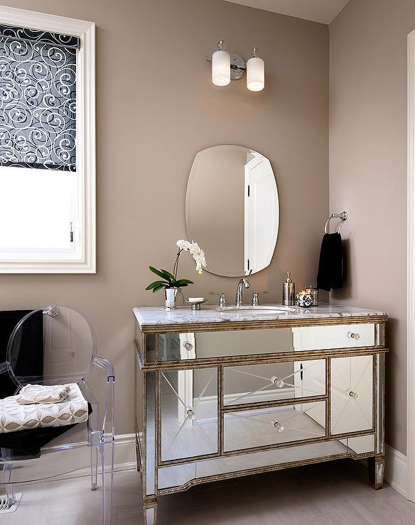 Glam Bathroom Features A Kartell Ghost Chair Placed Under Window Next To Mirrored Washstand Topped With White Marble And Curved Mirror