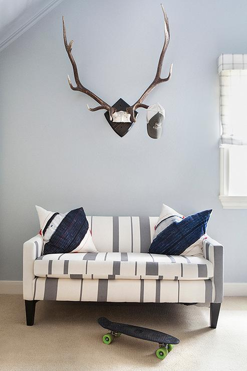 Gray Striped Sofa With Navy Pillows Under Faux Stag Head