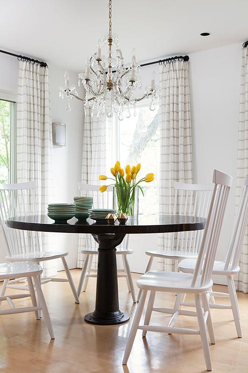 Contemporary Country Dining Room Features A Round Black Table Lined With White Windsor Chairs DWR Salt Illuminated By Crystal