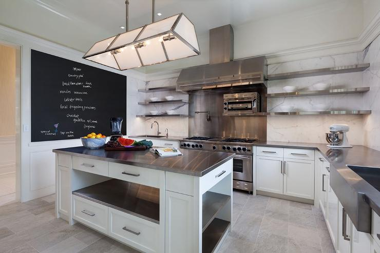 Elegant A Glass And Steel Industrial Chandelier Hangs Over A White Kitchen Island  Fitted With Stainless Steel Shelves As Well As A Stainless Steel Countertop  Facing ...
