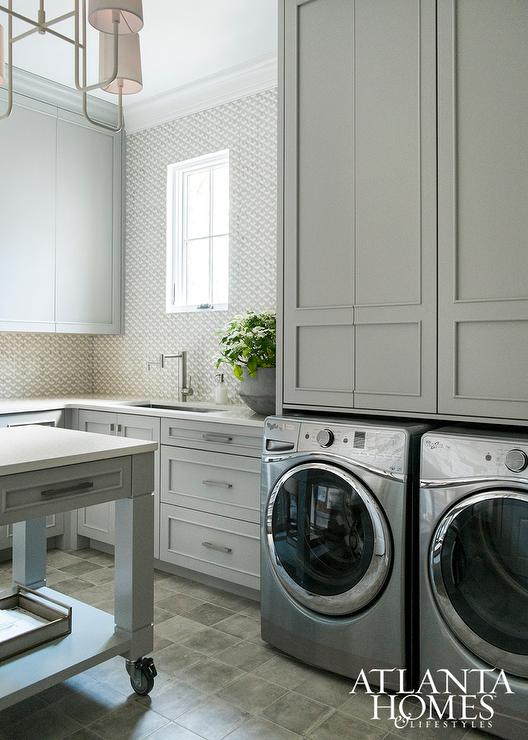 Gray laundry room cabinets with silver front load washer for Cupboards for laundry room