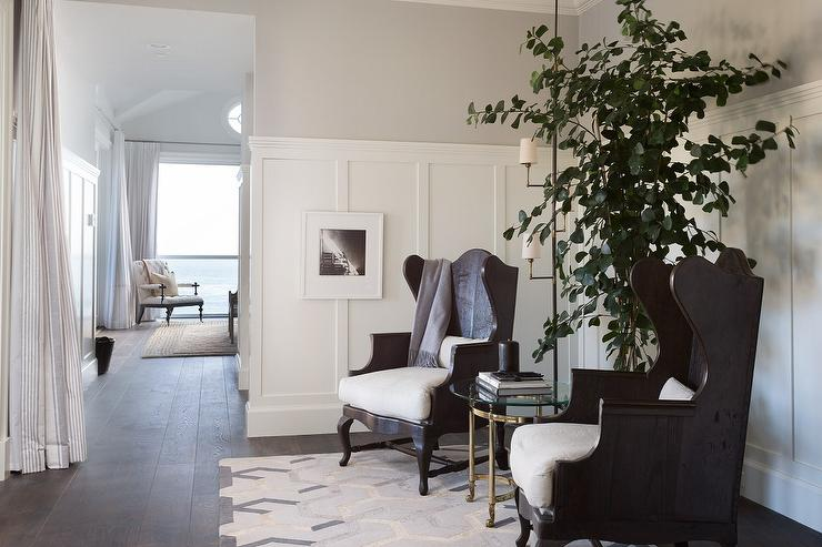 Foyer with black wingback chairs and gold and black floor for Foyer area furniture
