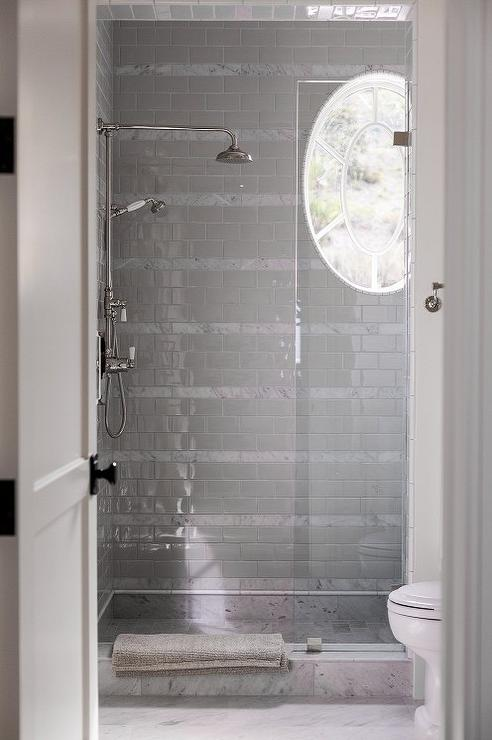 Elegant Chic Walk In Shower Features Gray Subway Tiles Accented With Strips Of  White Marble Lined With An Exposed Plumbing Shower Kit As Well As An Oval  Window. Nice Look