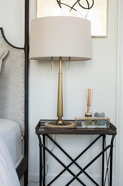 chic bedroom boasts a gray linen headboard on 4 poster bed next to a metal mirrored tray top bedside table and an antique brass lamp