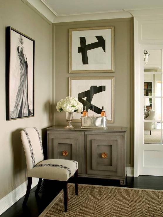 Taupe Dining Room Features Walls Painted Lined With A Gray Chest Adorned Gold Hardware Topped Sterling Silver Ice Bucker Placed Under