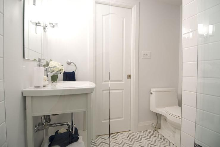 small white bathroom features a white washstand under a frameless
