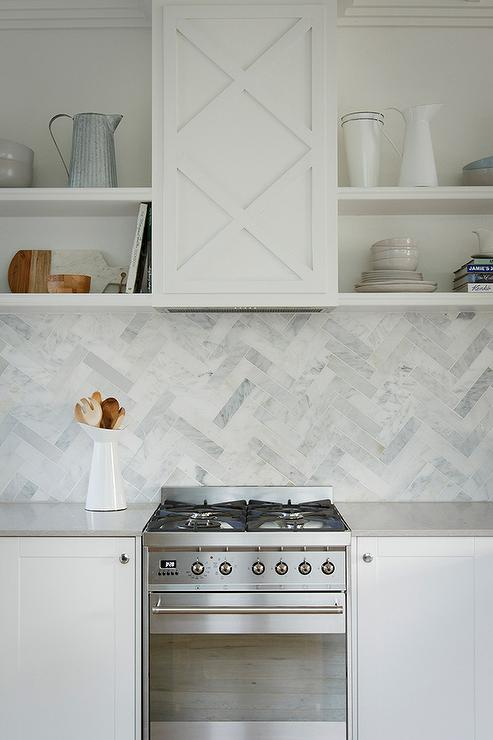 Chic Kitchen Features White Shaker Cabinets Paired With Light Gray Quartz  Countertops, Caesarstone Clamshell Quartz, And A Marble Herringbone  Backsplash.