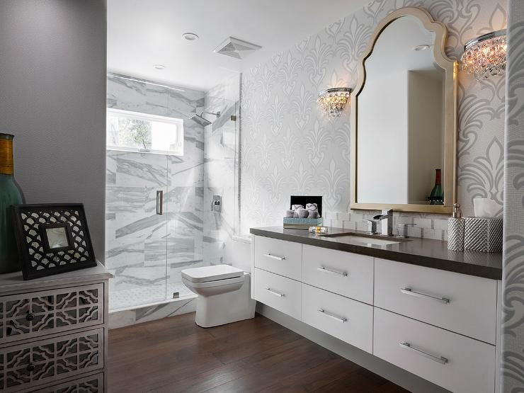 White Floating Vanity With Gray Quartz Countertop Under Gold Arched Mirror