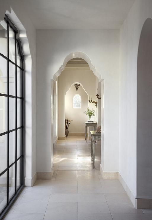 Long Hallway With Arched Doorways And Gray French Console