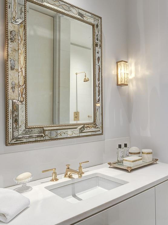 White And Gold Bathroom. White And Gold Bathroom Features An Antiqued Mirror Beveled Mirror Over A White Washstand Topped With White Quartz Fitted With A Sink And Gold Faucet Next