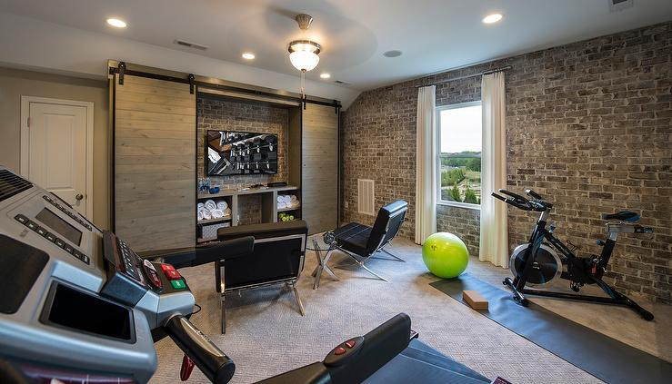 Industrial man cave and exercise room with exposed brick
