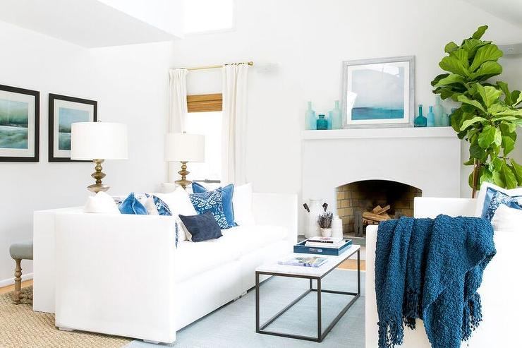 White And Blue Coastal Living Room Features White Shelter Back Sofas Draped  In Blue Pillows And Throw Blankets Facing Each Other Across From A Long ...