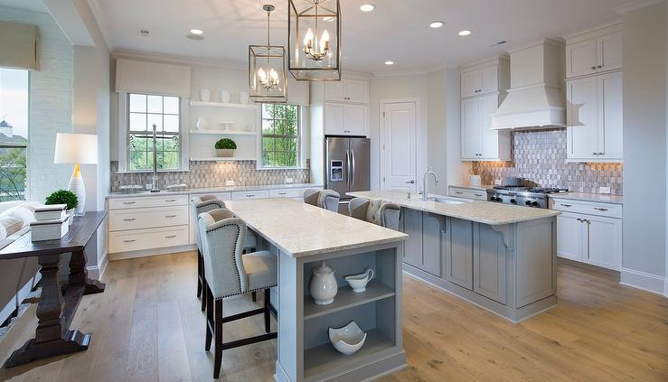 white gray kitchen 2. White and gray kitchen features white cabinets paired with granite  countertops a woven tiled backsplash A French hood stands Kitchen Island Freestanding Stove Transitional