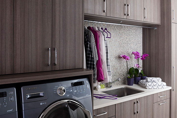 Contemporary Laundry Room Features Brown Melamine Cabinets Paired With A Gray Metallic Mosaic Tiled Backsplash Fitted With A Sink Placed Under A Tension Rod