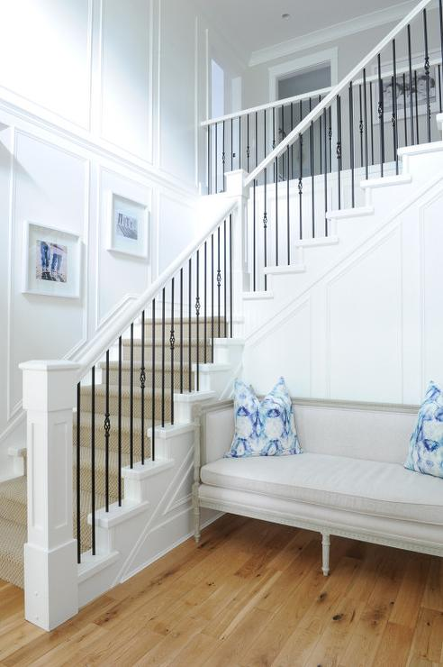 Chic Foyer Features A White Staircase Accented With Iron Spindles Lined  With A Sisal Rug.