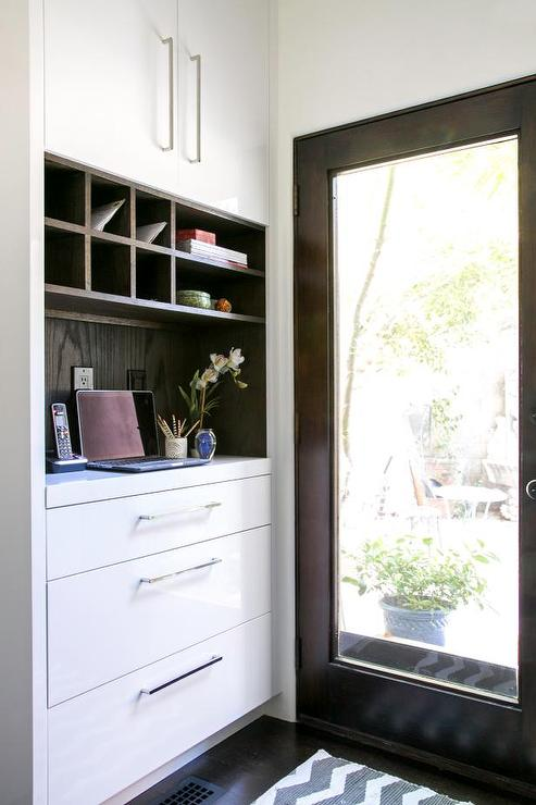 Glass paned back door design ideas message center fitted with dark stained oak wood pigeon cubby holes over a desk and stacked drawers next to a dark stained back door with a single glass planetlyrics Images