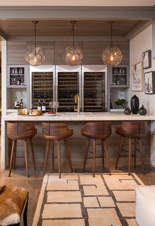 Marvelous Three Arteriors Beck Pendants Illuminate A Marble Waterfall Bar Fitted With  A Wet Bar Sink And Gold Gooseneck Faucet Lined With Wood Counter Stools.
