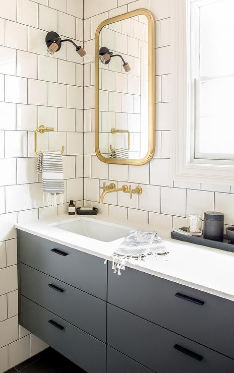 Chic Gray And Gold Bathroom Features Walls Clad In White Square Brick Tiles Accented With Dark Grout Lined A Curved Brass Mirror Restoration