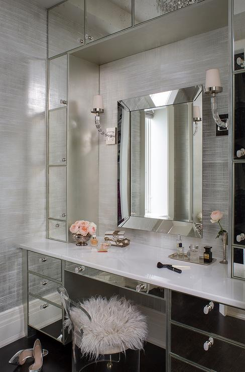 Glamorous Dressing Room Boasts A Mirrored Makeup Vanity Paired With A  Lucite Vanity Stool Under A Beveled Mirror Illuminated By Crystal Cube  Sconces ...