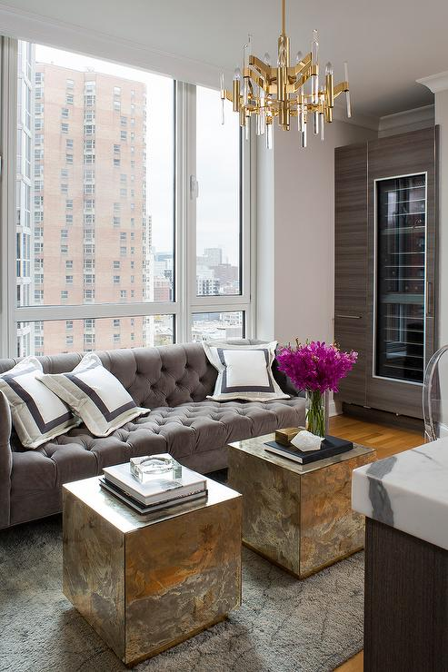 Chic glam living room features a gray tufted velvet sofa lined with