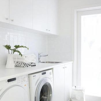 white and gray laundry room with gray backsplash tiles
