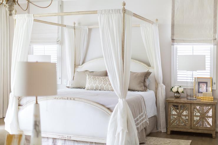 French bedroom features a white French canopy bed adorned with sheer  curtains tied to posts dressed in white and taupe bedding flanked by wood  nightstands ...
