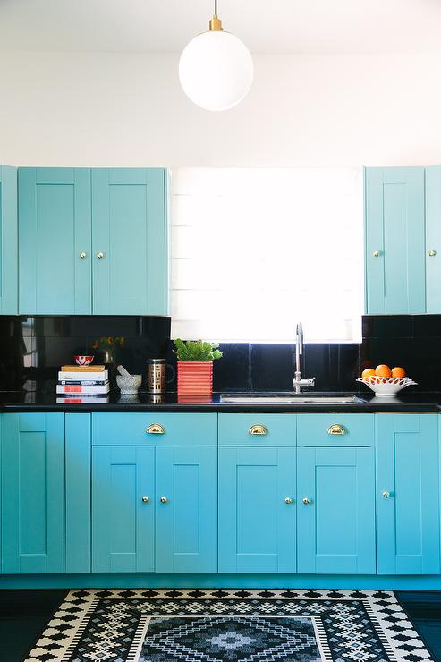 Contemporary Turquoise Blue Kitchen Features Cabinets Adorned With Polished Brass Cup Pulls Paired Glossy Black Countertops And Backsplash