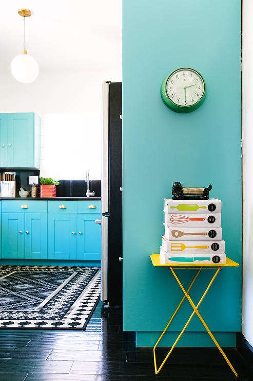 A Hallway Leading To A Turquoise Kitchen Is Lined With A Yellow Tray Table  Lined With Stacked Cookbooks And A Green Vintage Wall Clock.